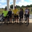 Five cyclists pose for a photo outdoors