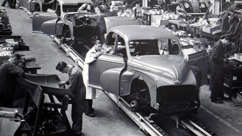 Black and white image of factory workers working in an assembly line building cars